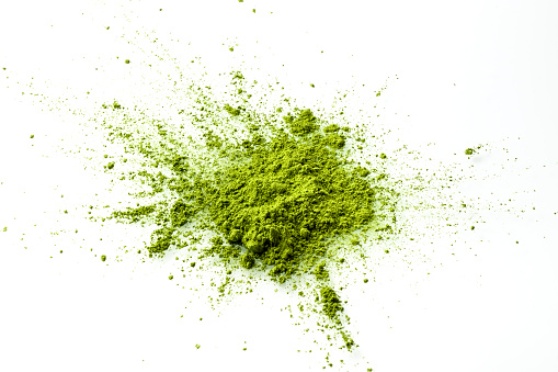 Matcha powder explosion on white background top view.