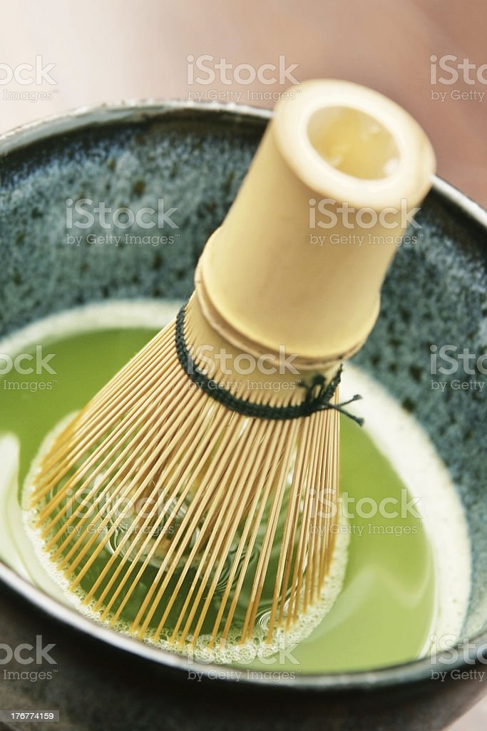 Matcha Tea being Stirred with Bamboo Whisk stock photo