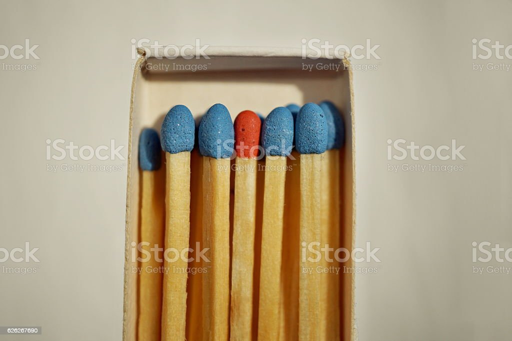 Matchbox full of matches with blue top and one different stock photo