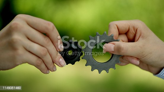 Two businesswomen trying to match cog gears. Flexibility in business