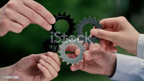 Business people trying to match cog gears. Teamwork, cooperation
