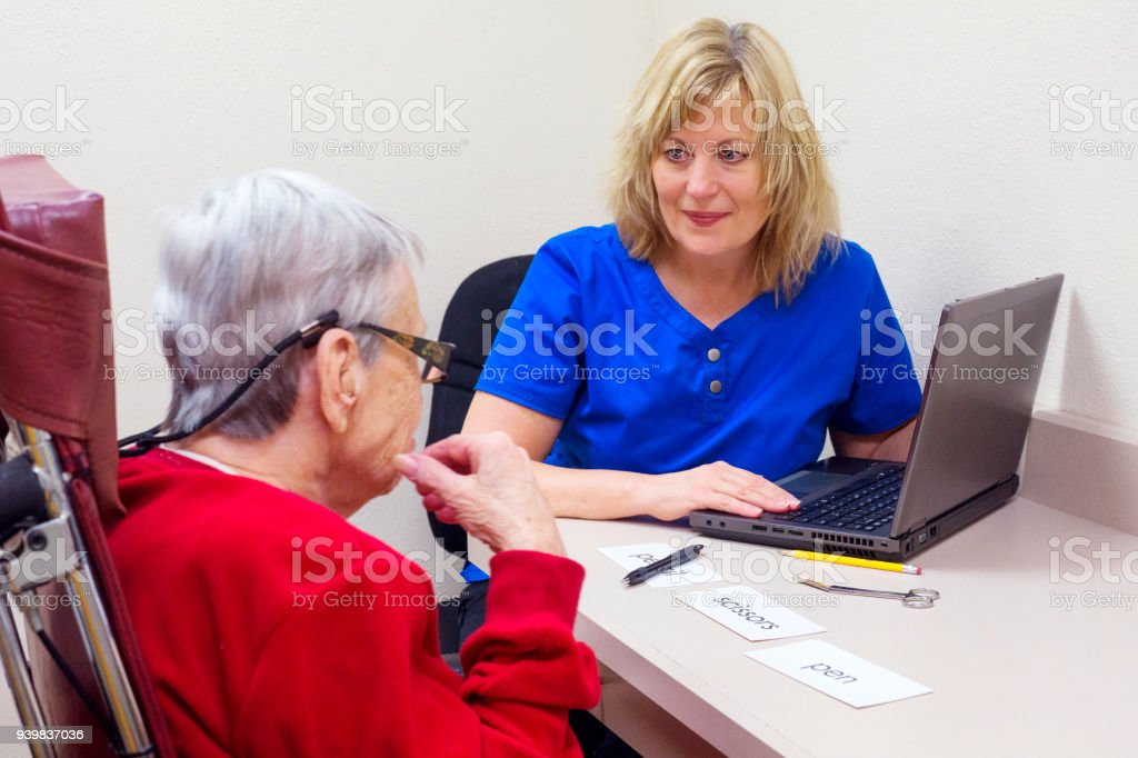 Matching objects to words in speech therapy to improve aphasia, or receptive language deficits stock photo