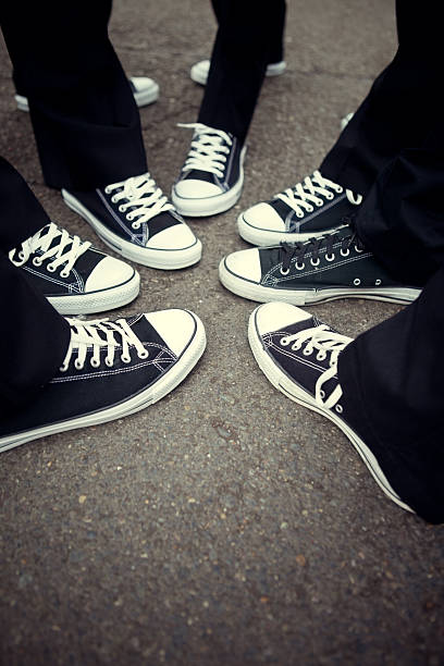 Matching Tennis Shoe Friendship A group of friends with matching black and white sneakers and black pants all put their feet together in a circle on a concrete cement background.  Vertical with copy space. all star stock pictures, royalty-free photos & images