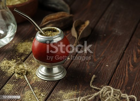 Mate yerba tea in calabash on wooden table. Traditional argentinian beverage.