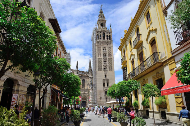 Mateos Gago street with La Giralda de Sevilla in the background. Seville, Spain - May 25, 2018: Mateos Gago street with La Giralda de Sevilla in the background. santa cruz seville stock pictures, royalty-free photos & images