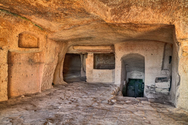 Matera, Basilicata, Italy: interior of an old cave house Matera, Basilicata, Italy: interior of an old cave house carved into the tufa rock in the old town (sassi di Matera) tuff stock pictures, royalty-free photos & images