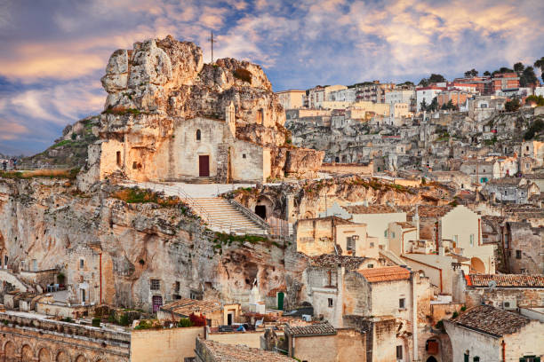 Matera, Basilicata, Italy: landscape of the old town with the rock church Santa Maria de Idris Matera, Basilicata, Italy: landscape at sunset of the old town (sassi di Matera) with the rock church Santa Maria de Idris matera italy stock pictures, royalty-free photos & images
