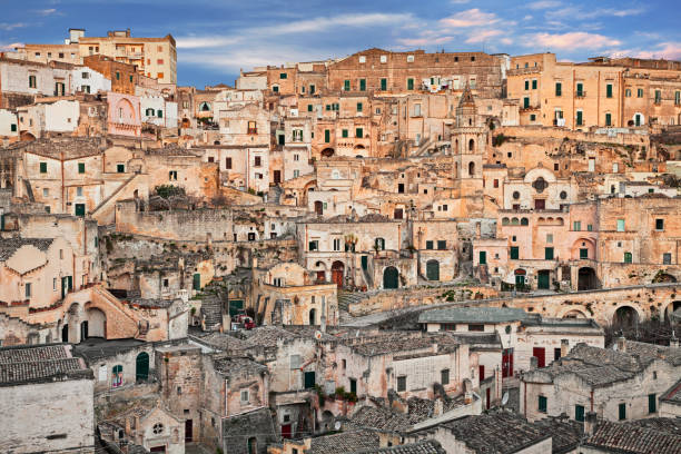 Matera, Basilicata, Italy: view at sunrise of the old town Matera, Basilicata, Italy: cityscape at sunrise of the picturesque old town (sassi di Matera) with the characteristics ancient tuff houses matera italy stock pictures, royalty-free photos & images