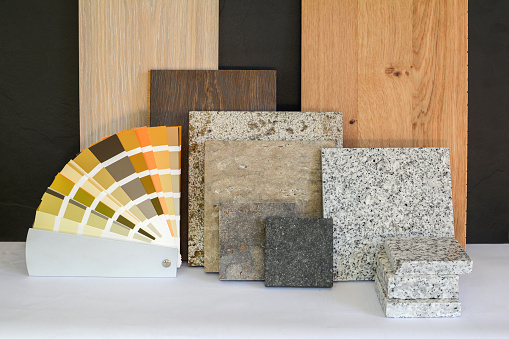 Material collage with natural stone, tiles, wooden parquet floor and color card for renovation of an apartment building