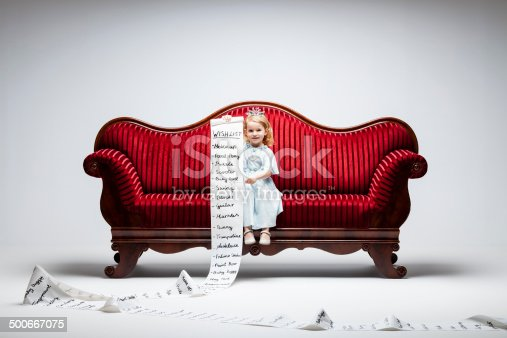 3 year princess girl sitting on red vintage sofa and holding an extraordinary long list of material whishes.