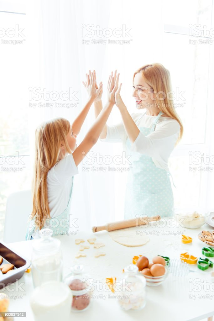 Maternity parenthood white light win winner tasty finished complete concept. Vertical side view photo of cheerful excited cute lovely sweet charming mommy small kid giving high-five in light kitchen stock photo