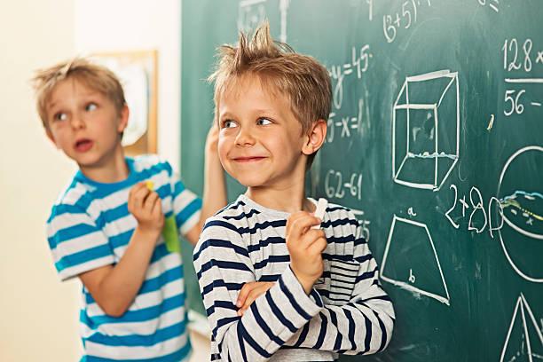 math es la diversión de los niños de pie en la pizarra - geometría fotografías e imágenes de stock