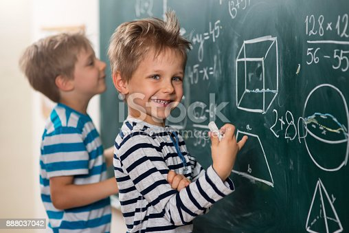 istock Math is fun - boys standing at the blackboard 888037042