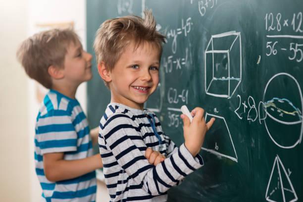 計算は楽しい男の子、黒板に立つ ストックフォト