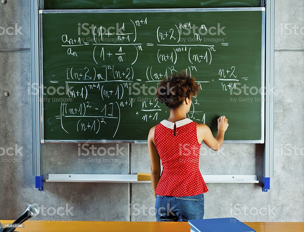 Math lesson Back view of teenaged girl writing a formula on a blackboard.  18-19 Years Stock Photo