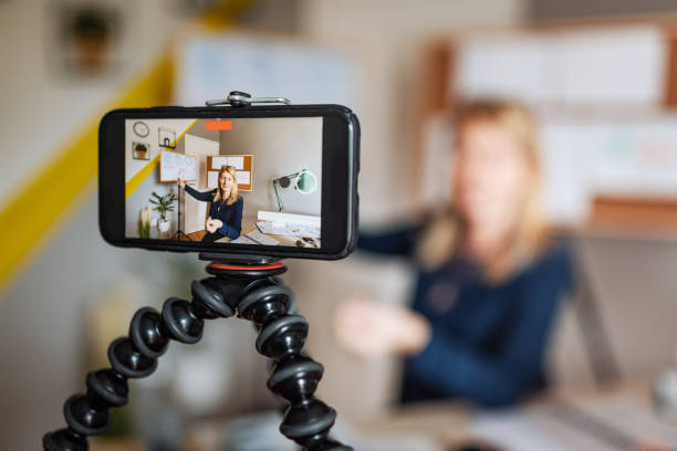 Math professor at home, looking and talking direct to camera during online classroom stock photo