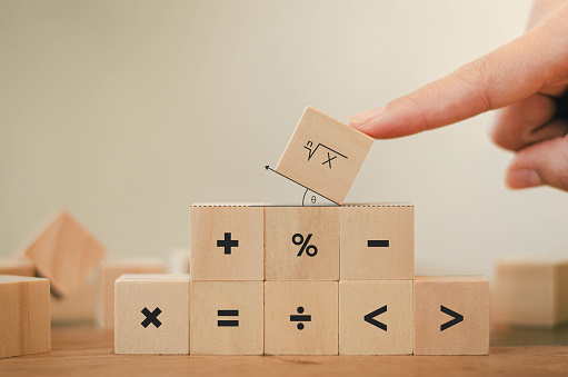 Math symbols written on the wooden blocks of a businessman With calculations with ideas A concept, a difficult problem or a mathematical solution