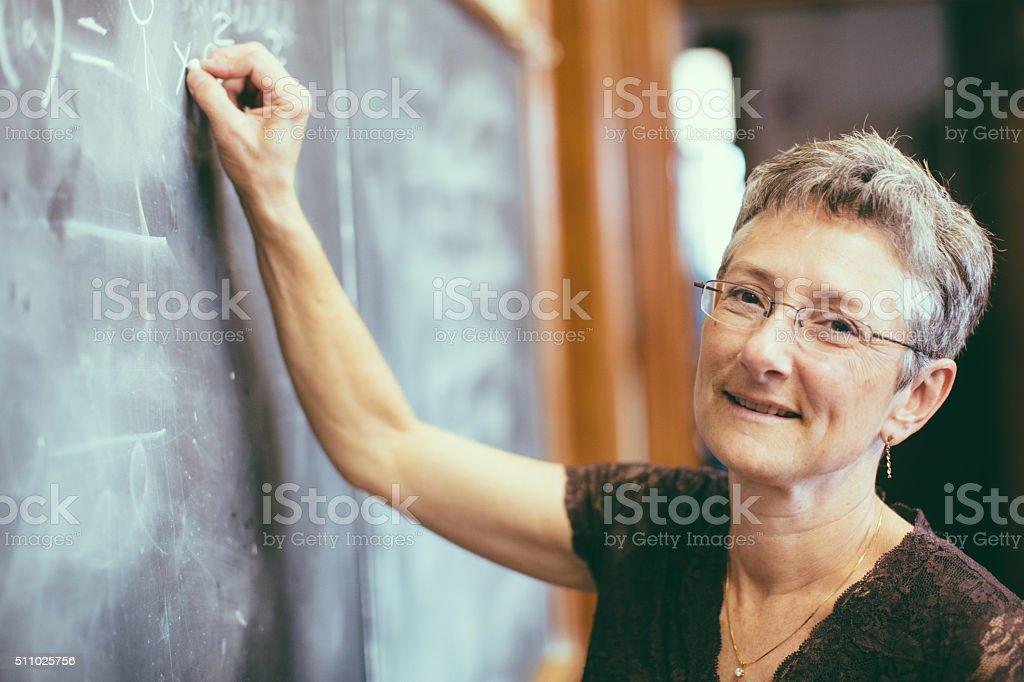 Math teacher at chalkboard writing formula stock photo