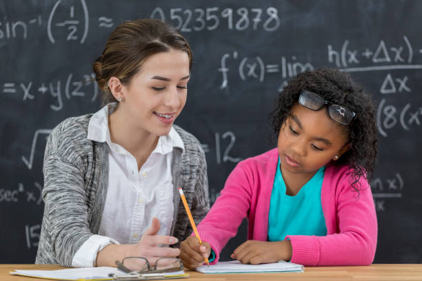 math teacher helps elementary schoolgirl with math assignment - math class stock photos and pictures