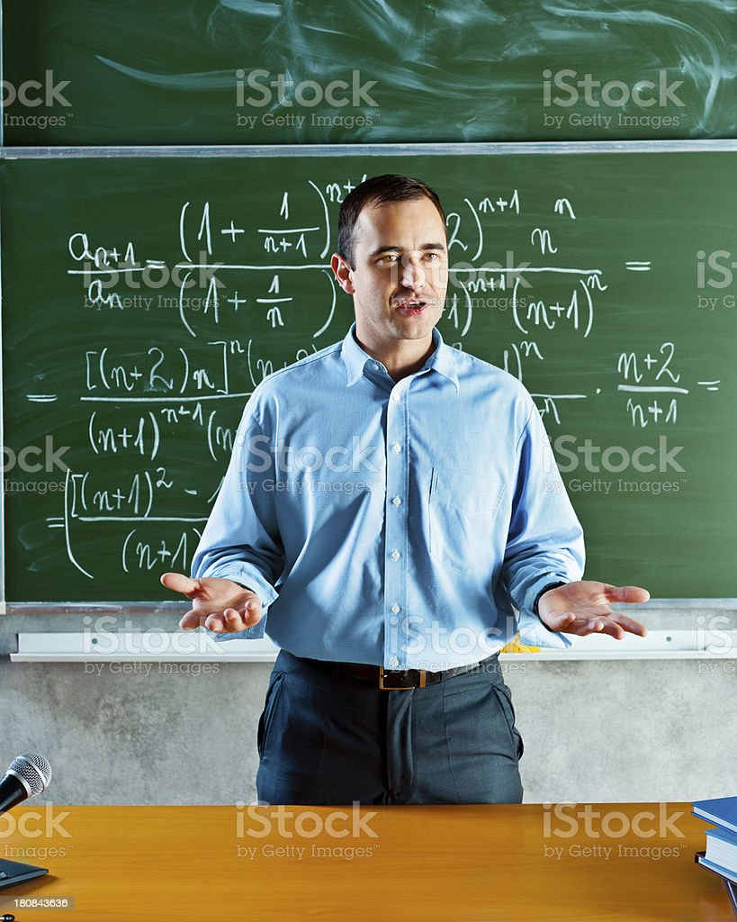 Math Teacher Math teacher standing against blackboard full of formulas and giving a lecture. 30-39 Years Stock Photo