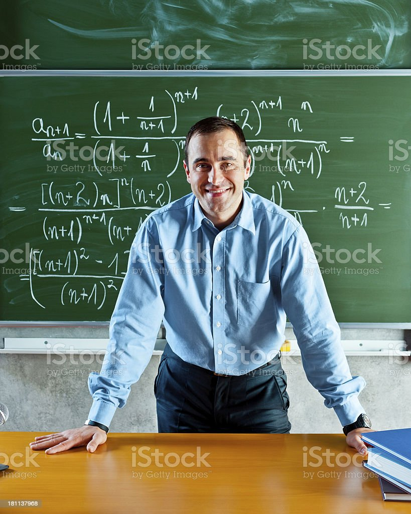 Math Teacher Math teacher standing against blackboard full of formulas and smiling at the camera. 30-39 Years Stock Photo