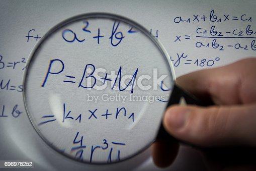 istock Mathematical formulas viewed through a magnifying glass 696978252