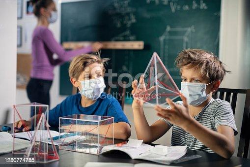 Little boys in school classroom wearing face masks. Teacher in the background is writing on the blackboard. Nikon D850