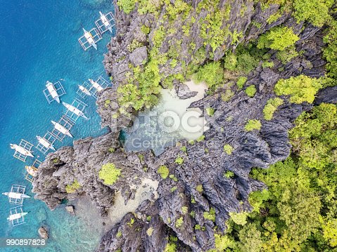 View down to beautiful behind rock formation hidden beach on majestic Matinloc Island with typical filipino Balangay Tourist Tour Boats anchored in front of the rock formations from where you can swim into the beautiful natural rock lagoon and small beach. Aerial Drone Point of View. Matinloc Island, Mimaropa, El Nido, Palawan, Philippines, Asia