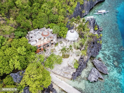 Aerial view towards the Matinloc Shrine on the west coast of Matinloc Island. Matinloc Shrine - also known as Shrine of Our Lady of Matinloc - is an abandoned site hidden at the foot of towering karst cliffs on the western coast of Matinloc Island. Aerial Drone Point of View. Tapiutan Island, Mimaropa, El Nido, Palawan, Philippines, Asia