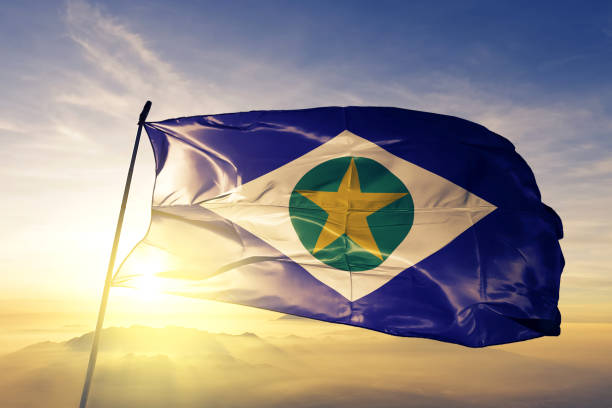 Mato Grosso state of Brazil flag textile cloth fabric waving on the top sunrise mist fog stock photo