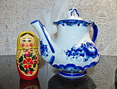 Matryoshka and teapot in the style of Gzhel. Matryoshka-Russian folding doll made of wood, inside which there are dolls of smaller size. Gzhel-Russian folk craft of ceramics and production porcelain. Souvenirs