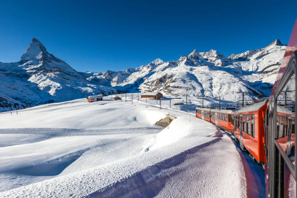 matterhorn and gornergrat railway in the swiss alps beautiful matterhorn mountain under blue sky in winter wonderland with the red gornergrat railway in the swiss alps, switzerland, europe. zermatt stock pictures, royalty-free photos & images