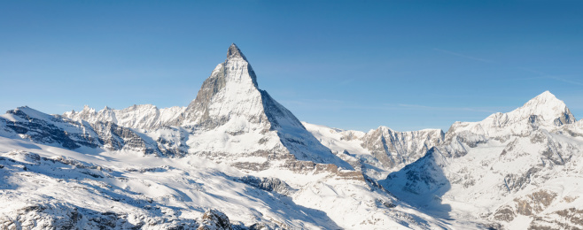 An alpine panorama featuring the iconic peak of the Matterhorn in Switzerland, photographed in winter.