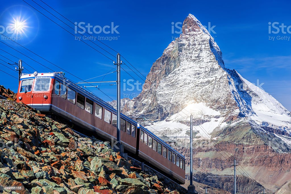 Matterhorn peak against  train in Swiss Alps stock photo