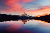 Splendid landscape with colorful sunrise on Stellisee lake. Snowy Matterhorn Cervino peak with reflection in clear water. Zermatt, Swiss Alps