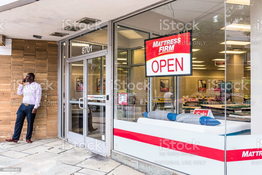 Mattress firm warehouse store entrance facade and sign with salesman...