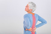 istock Matur Woman suffering from lower back pain. Mature woman resting with back pain. Female lower back pain. Senior woman injury suffering from backache, Spine in 3d 1190369828