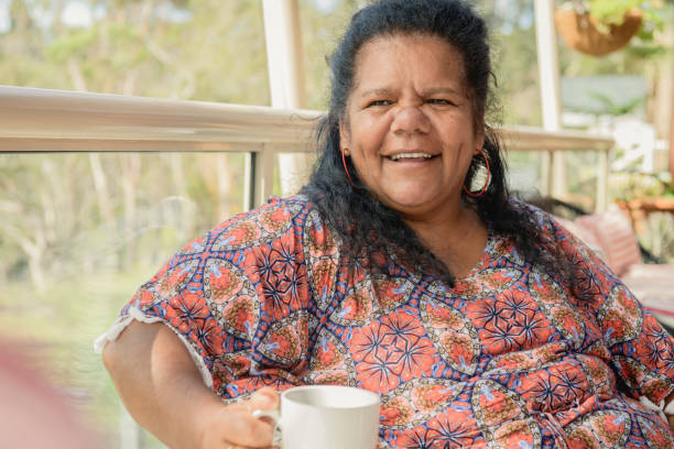 Mature Aboriginal woman holding coffee cup and looking away stock photo