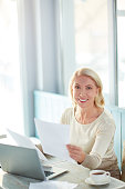 Happy mature businesswoman with papers sitting by workplace, working with financial documents and looking at camera