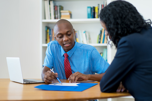 istock Mature adult african american businessman talking to employee 1210046517