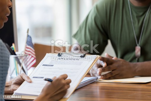 A mid adult African American bank manager fills out a loan application while an African American soldier looks on.