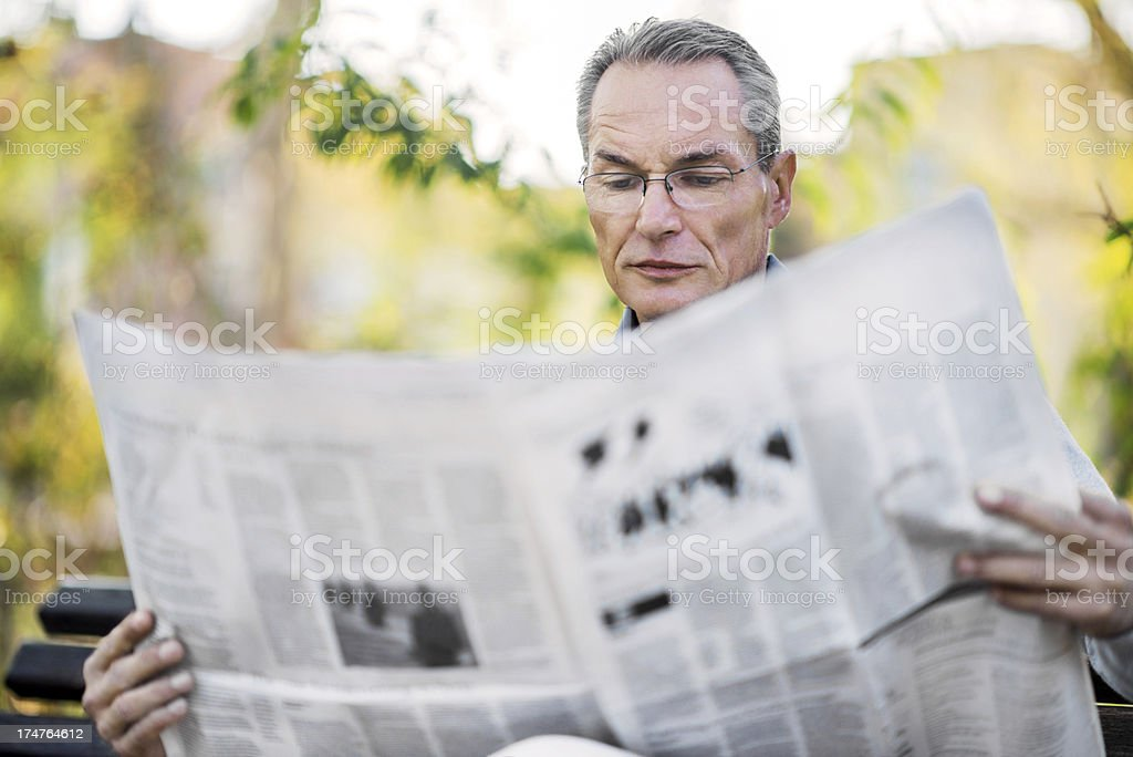 Mature adult businessman reading newspapers royalty-free stock photo