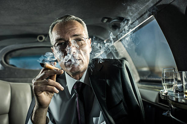 mature adult businessman smoking a cigar in limousine. - guy with cigar stockfoto's en -beelden