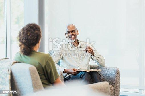 Mature adult counselor laughs when client tells joke