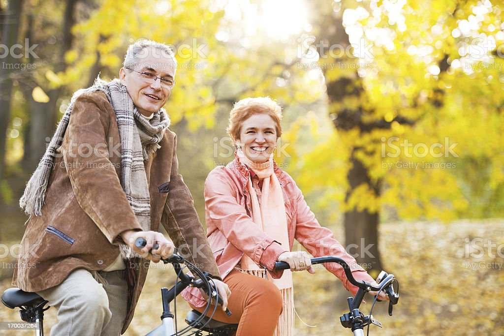 Mature adult couple riding bicycles in park. royalty-free stock photo