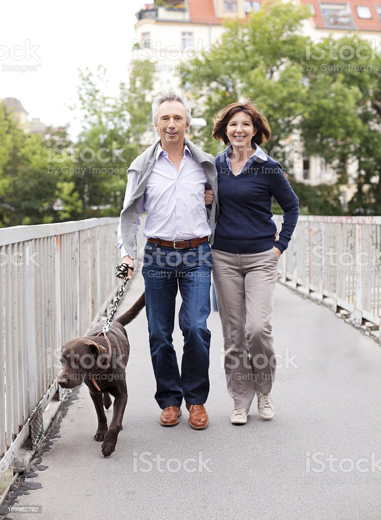 Mature Adult Couple walking the dog stock photo