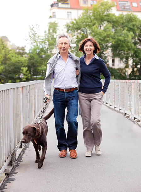 mature adult couple walking the dog - mid adult couple stock pictures, royalty-free photos & images