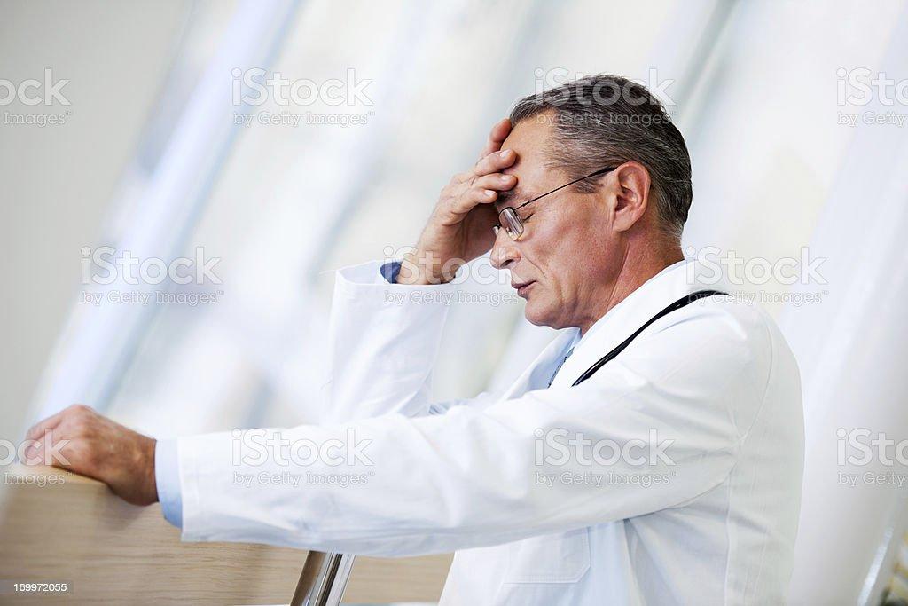 Mature adult doctor having a headache. stock photo
