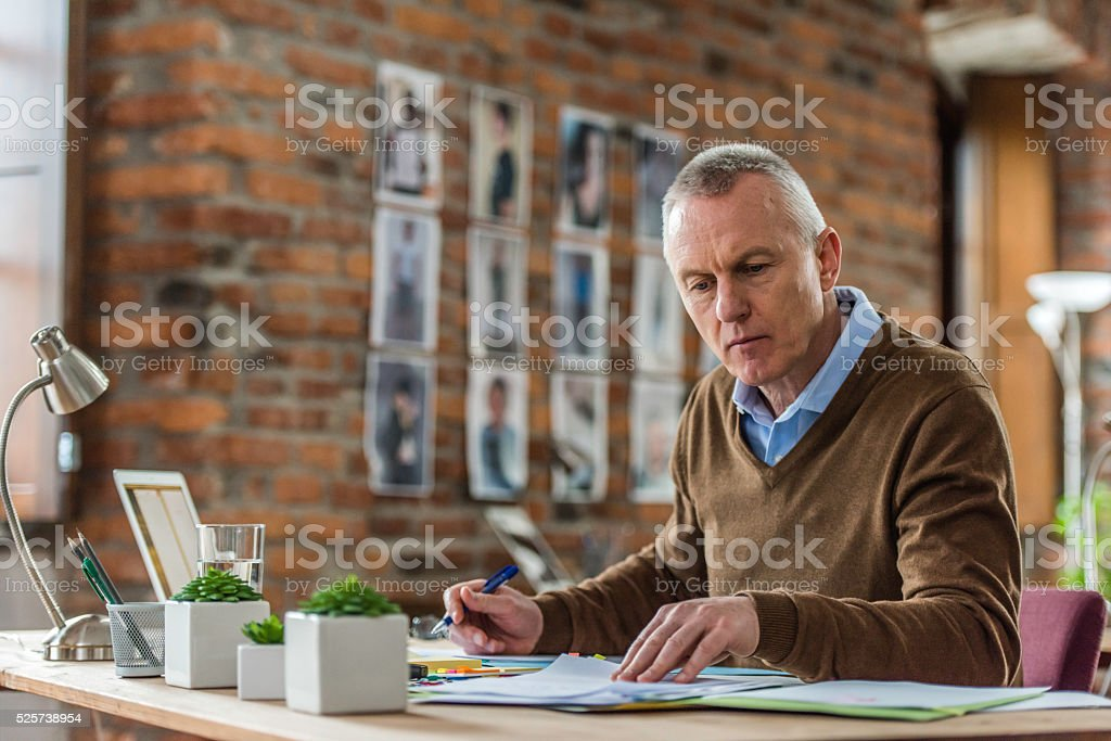 Mature adult enterpreneur reviewing his papers Older businessman sitting behind a desk in the office and looking at some papers. 50-59 Years Stock Photo