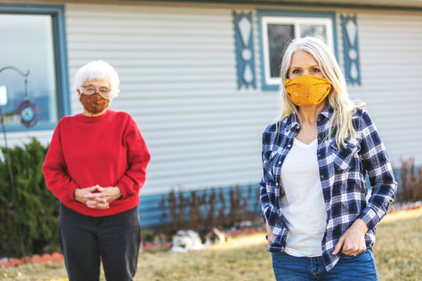 Mature Adult Female and Senior Adult Female Wearing Face Masks and Demonstrating Social Distancing Due to Infectious Virus Outbreak Pandemic stock photo
